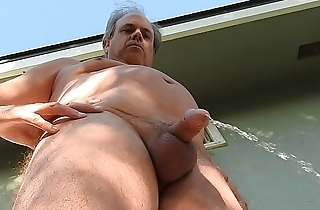 A naked daddy taking a pee outdoors on his back patio.